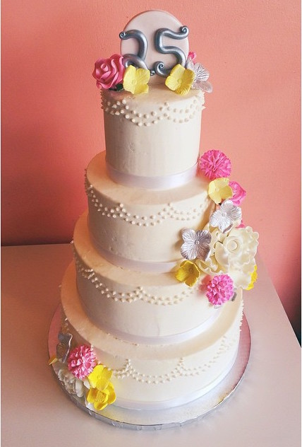 White buttercream anniversary cake with pink and yellow sugar flowers