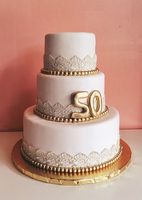 Blush fondant anniversary cake with vintage lace and gold accents