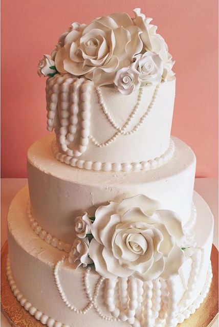 White buttercream anniversary cake with fondant pearls and sugar flowers