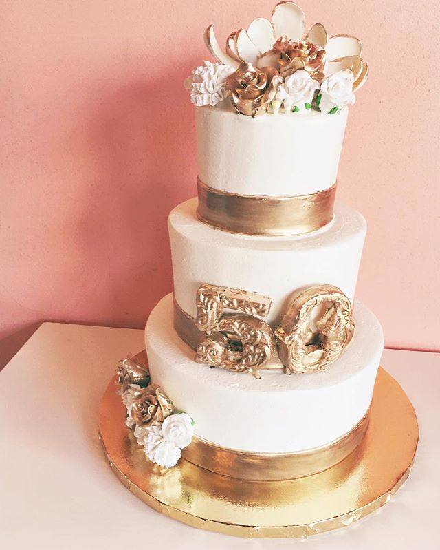 White buttercream cake with gold fondant accents