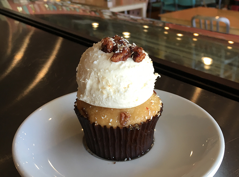 Italian Cream-coconut cake with pecans baked into the batter topped with a scoop of cream cheese icing and candied pecan clusters